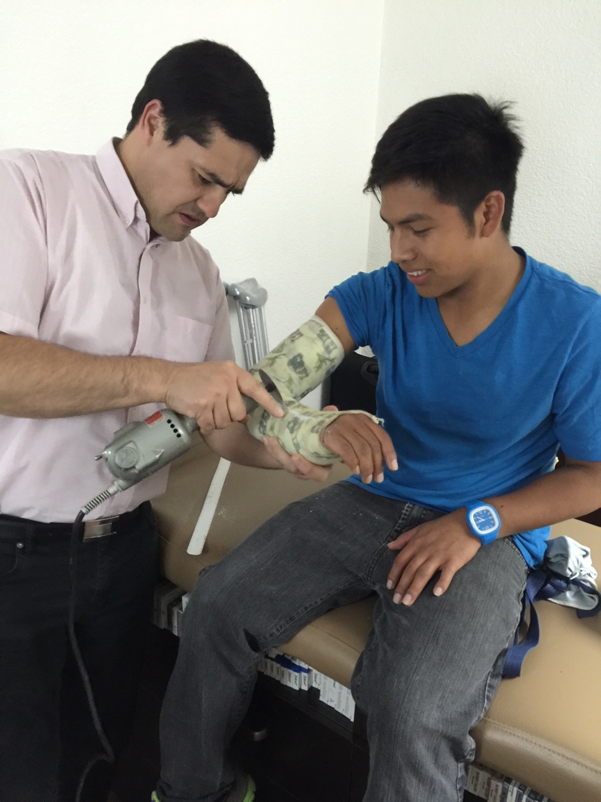 Dr Miguel taking off Bryan's cast