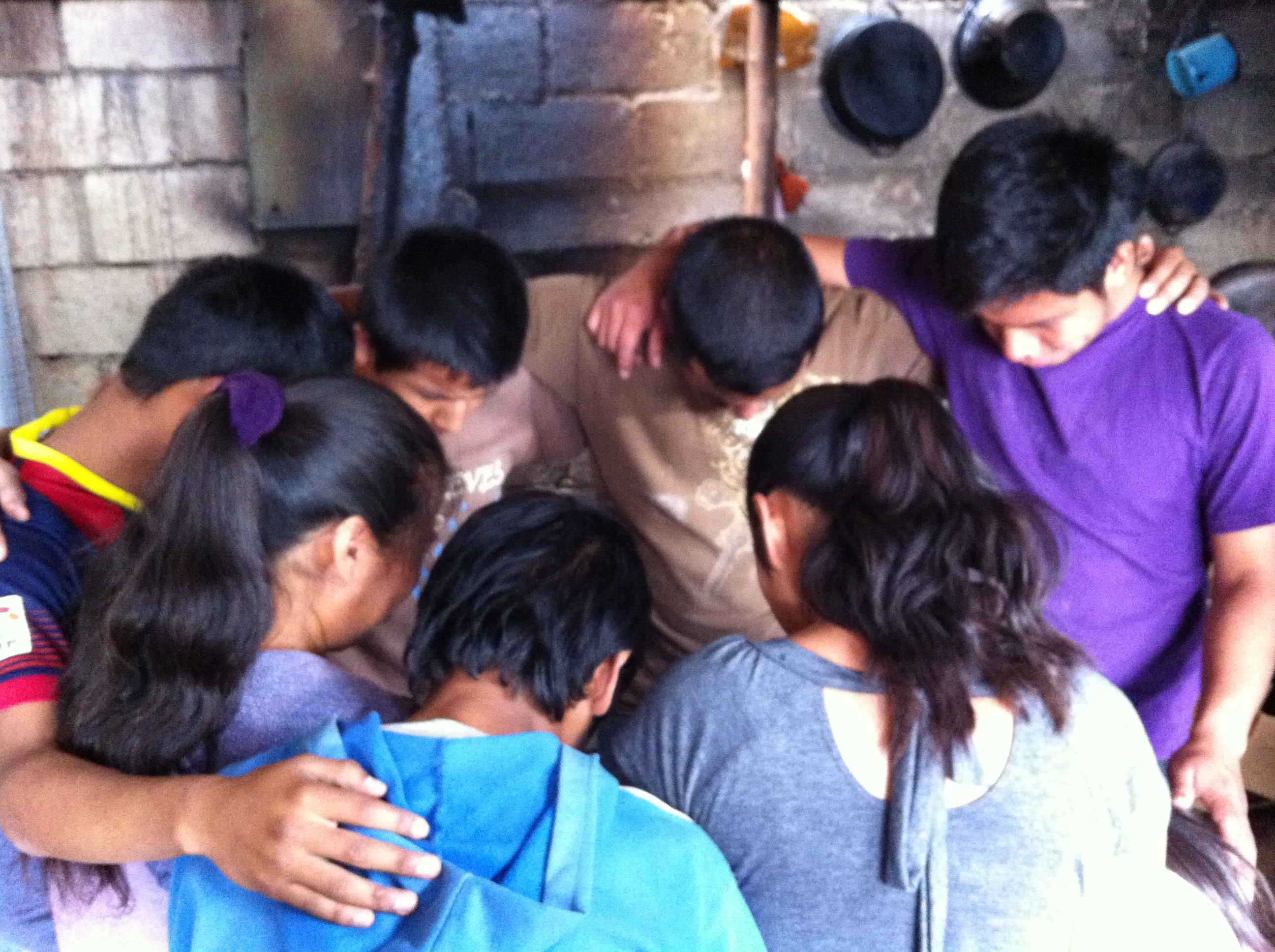 Boys prayin after the 1st installation of a stove for the poor family