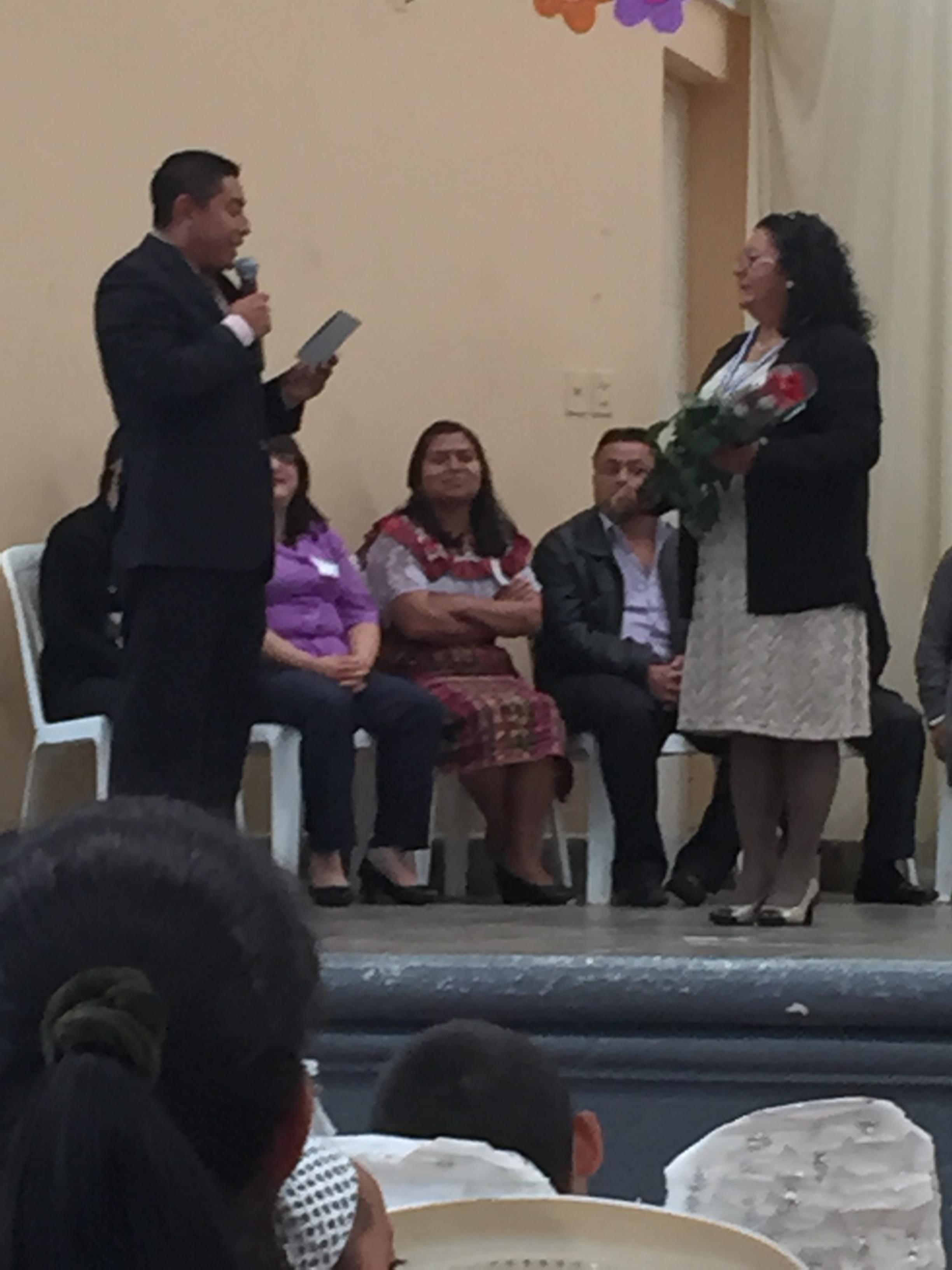 Professor Albert presenting flowers to the Secretary of Education