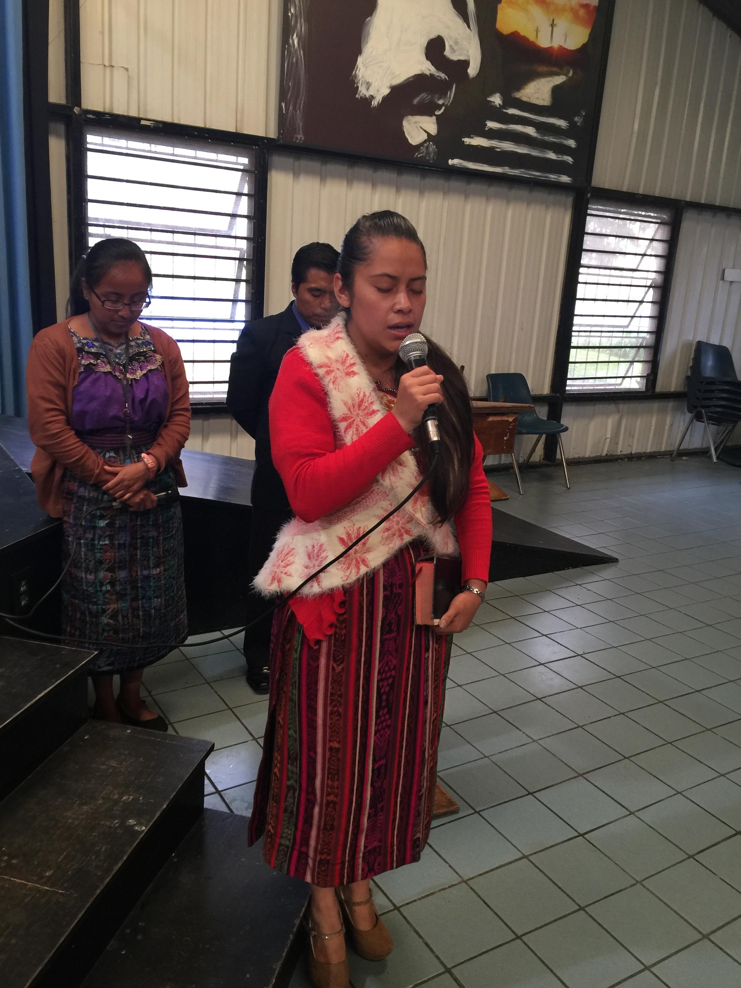 A teacher praying for the children at closing ceremonies.